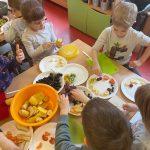 dzieci wykonują sałatkę owocową